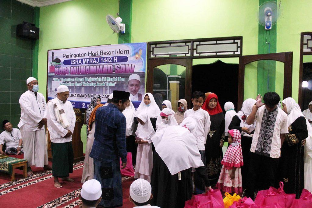 Pemberian santunan anak yatim yang diwakili oleh Ketua DKM Masjid Al-Amanah Jamhari, Ustad Muhammad Ma'ruf Amin, dan Ketua RW09 Imam Susilo. (Foto: OvanTaufik)